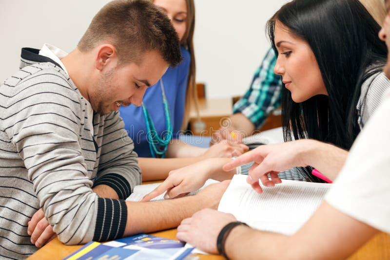 Jonge studenten die samen met nota's zitten stock afbeeldingen