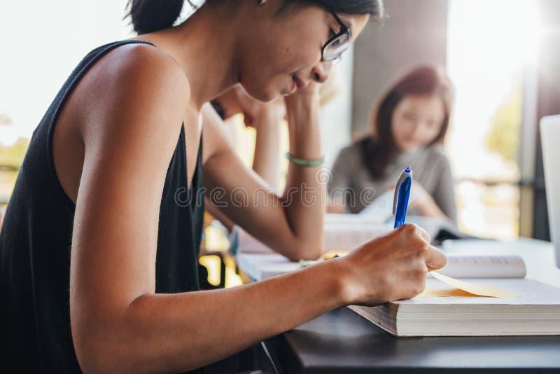 Jonge studenten die in universitaire bibliotheek bestuderen stock foto's