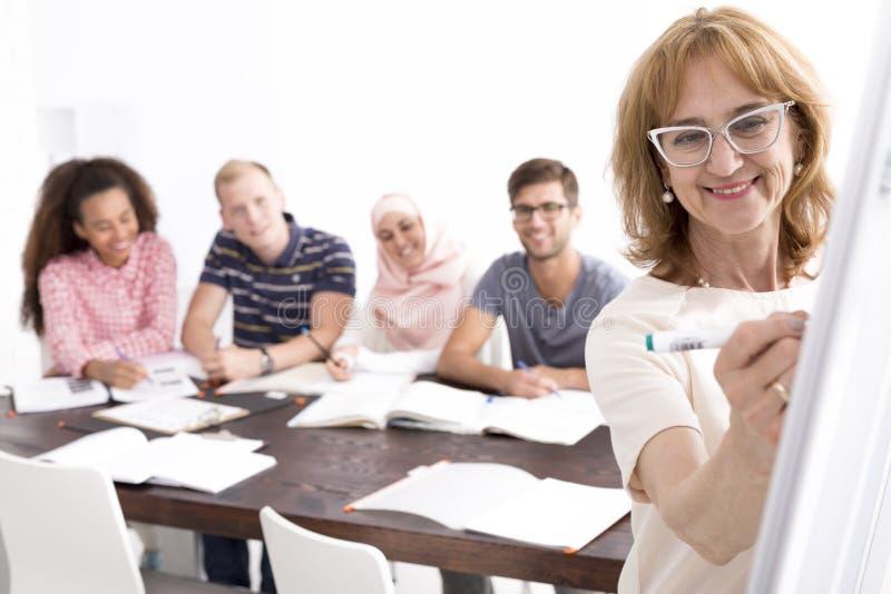 Jonge studenten en hun leraar stock foto