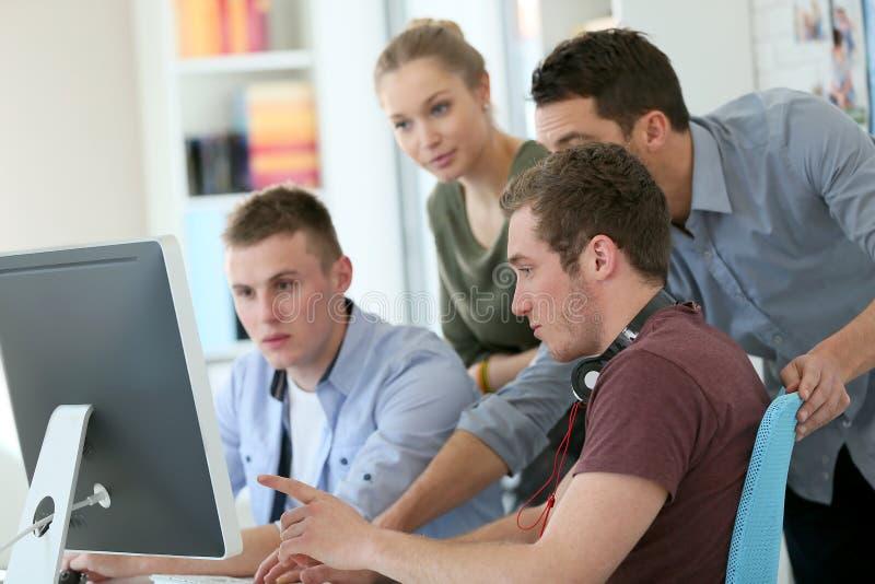 Jonge studenten met professor achter de computer stock afbeelding
