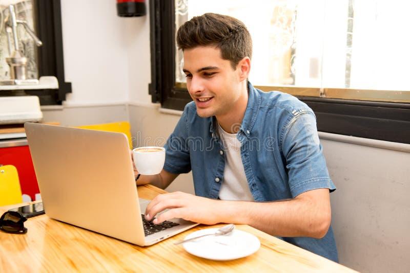 Jonge studentenmens die en op computer in koffiewinkel werken bestuderen stock foto's