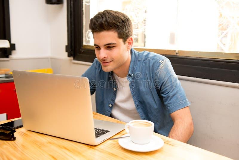 Jonge studentenmens die en op computer in koffiewinkel werken bestuderen stock foto