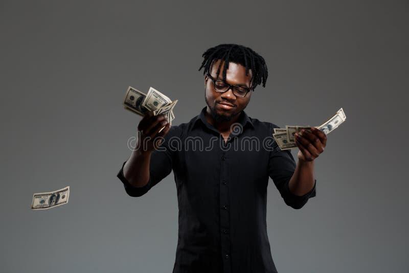 Jonge succesvolle Afrikaanse zakenman die geld over donkere achtergrond werpen royalty-vrije stock afbeeldingen
