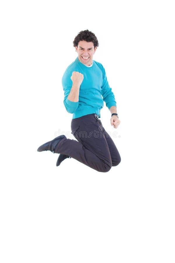 Jonge succesvolle mens die uit vreugde springen die geluk uitdrukken royalty-vrije stock foto's