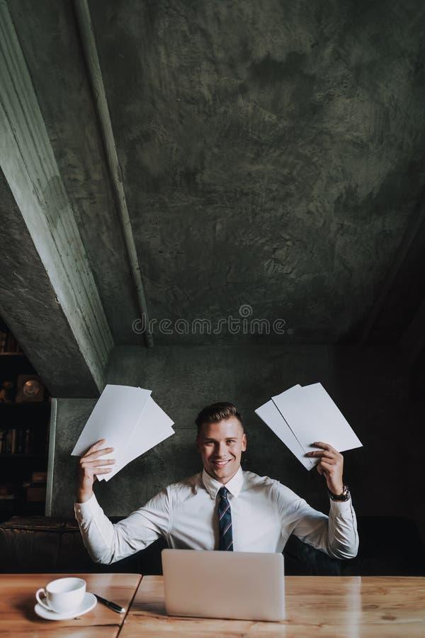 Jonge succesvolle mens die vele document bladen houden royalty-vrije stock afbeelding