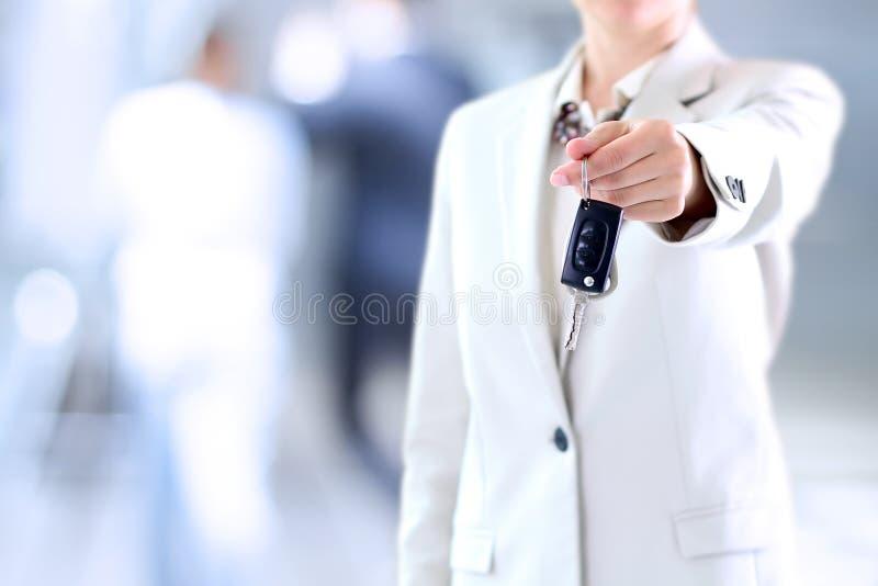 Jonge succesvolle onderneemster die een autosleutel aanbieden stock foto