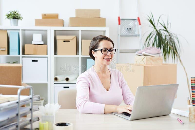 Jonge succesvolle onderneemster die online winkelen stock afbeelding