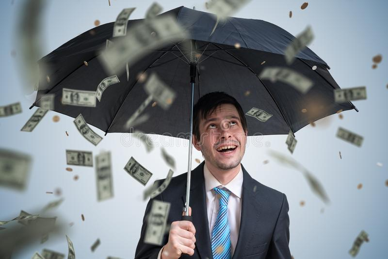 Jonge succesvolle rijke zakenman met paraplu en geld die neer vallen royalty-vrije stock afbeeldingen