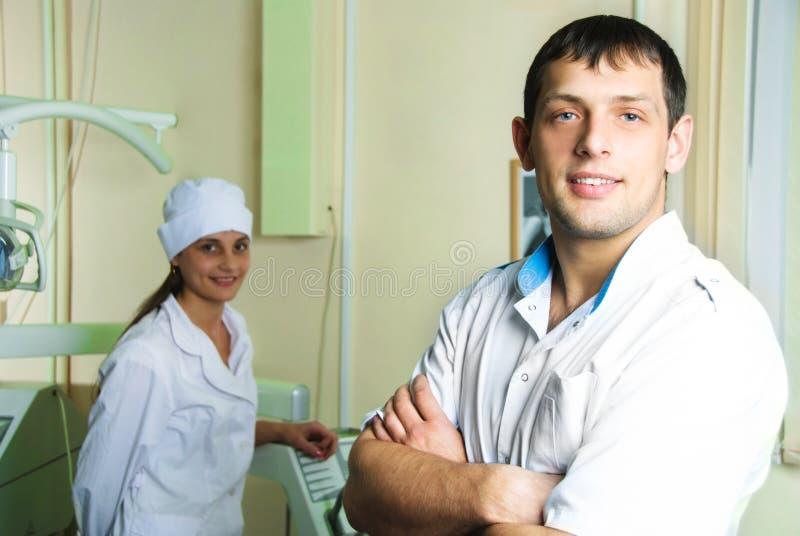 Jonge succesvolle tandarts met zijn medewerker royalty-vrije stock fotografie
