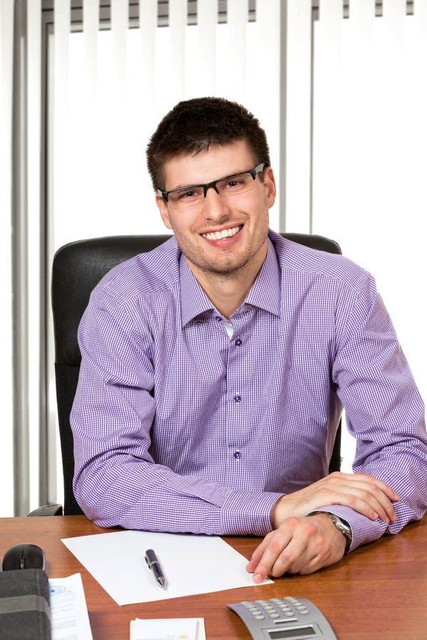 Jonge succesvolle zakenman die bij zijn bureau werken stock foto's