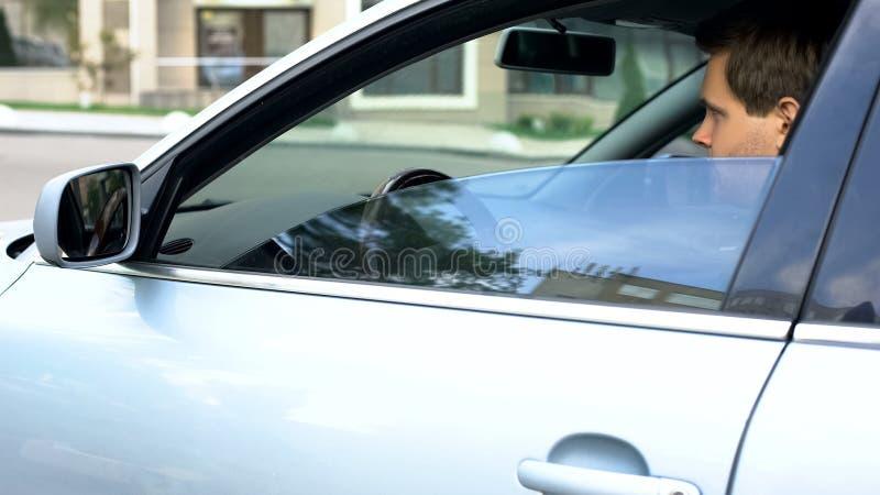 Jonge succesvolle zakenmanzitting op bestuurderszetel van auto, klaar om voor het werk te gaan stock fotografie