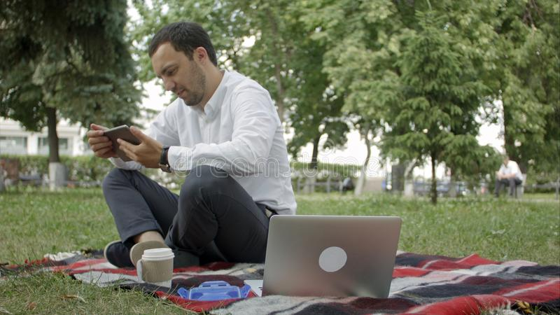 Jonge succeszakenman die tablet, laptop, mobiele telefoon in het park gebruiken royalty-vrije stock afbeeldingen