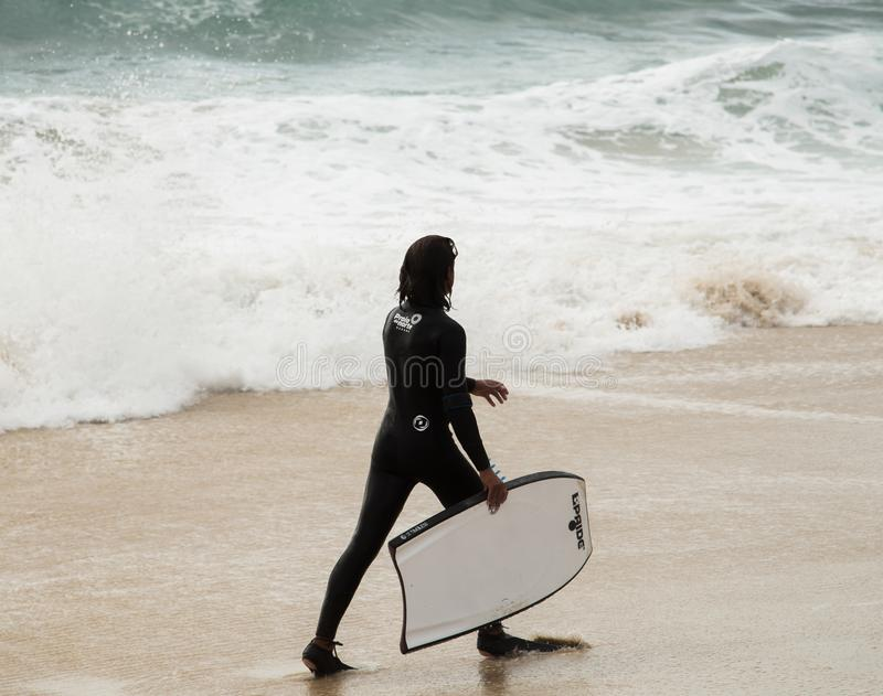 Jonge surfer en de oceaangolven stock foto's