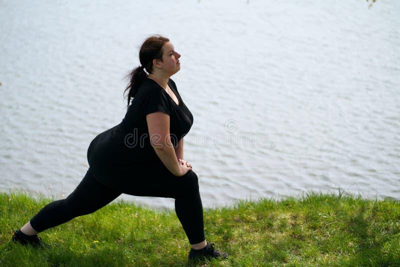 Jonge te zware vrouw die ochtendyoga doen stock fotografie