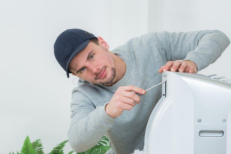 Jonge technicus die airconditioningssysteem binnen installeren stock afbeeldingen