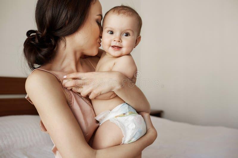Jonge tedere gelukkige moeder die haar pasgeboren baby het glimlachen zitting op bed in ochtend koesteren stock afbeelding