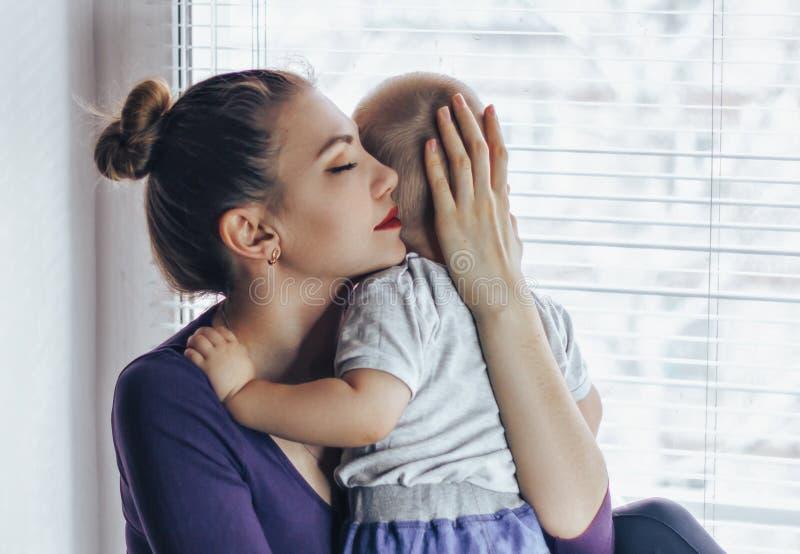Jonge tedere gelukkige moeder die haar pasgeboren baby het glimlachen zitting op vensterbank in ochtend koesteren Het genieten va royalty-vrije stock foto's