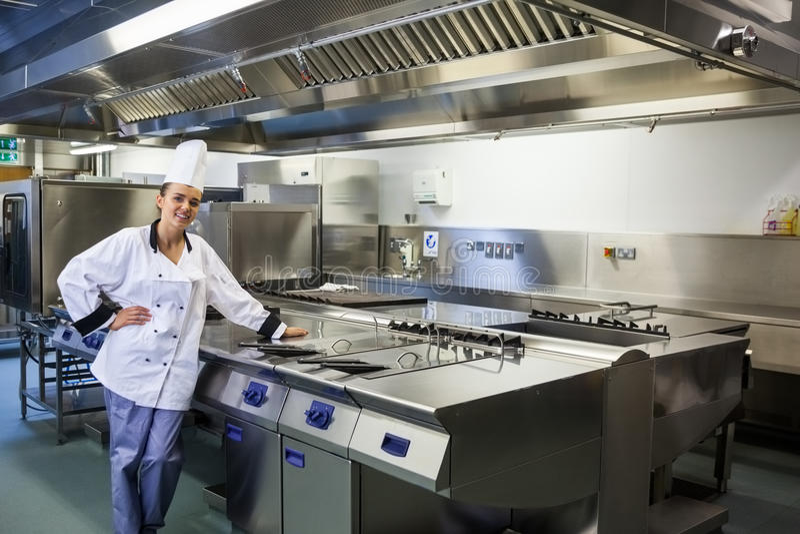Jonge tevreden chef-kok die zich naast het werkoppervlakte bevinden stock foto's
