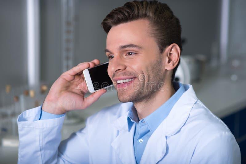 Jonge tevreden deskundige die en telefoongesprek glimlachen hebben stock fotografie