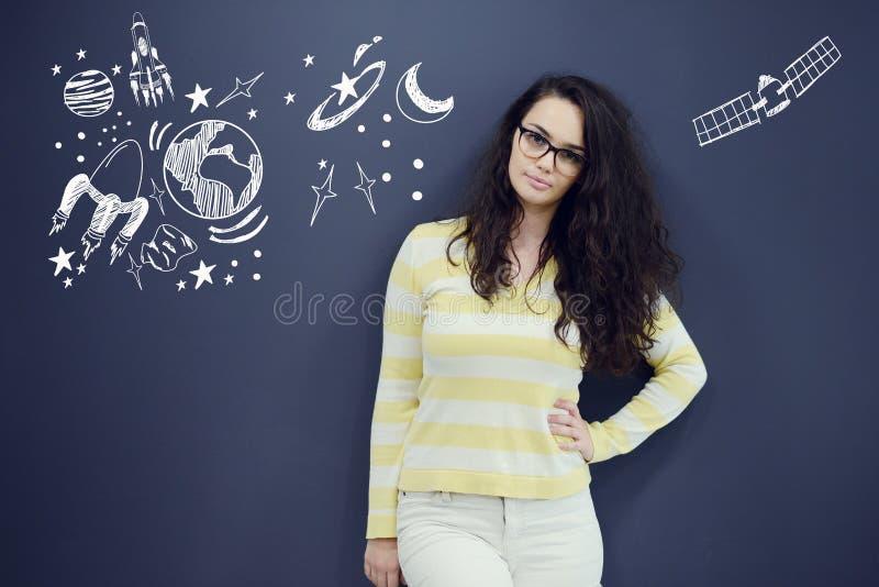 Jonge thinkful vrouw op blauwe grijze achtergrond met universumpictogrammen royalty-vrije stock afbeeldingen