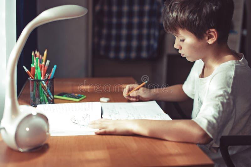 Jonge thuiswerk doen of schooljongen die thuis leren stock fotografie