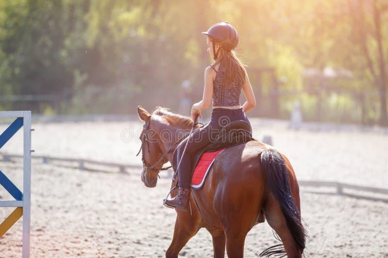 Jonge tiener die haar paard berijden bij opleiding stock foto