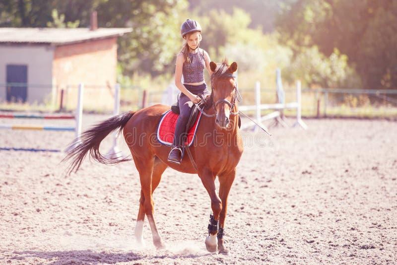 Jonge tiener die haar paard berijden bij opleiding stock fotografie