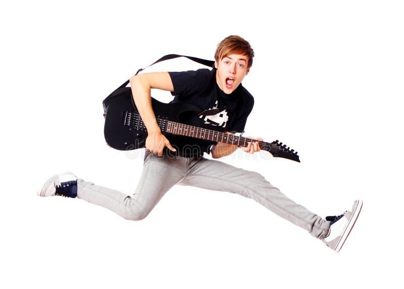 Jonge tiener die met gitaar springt stock foto's
