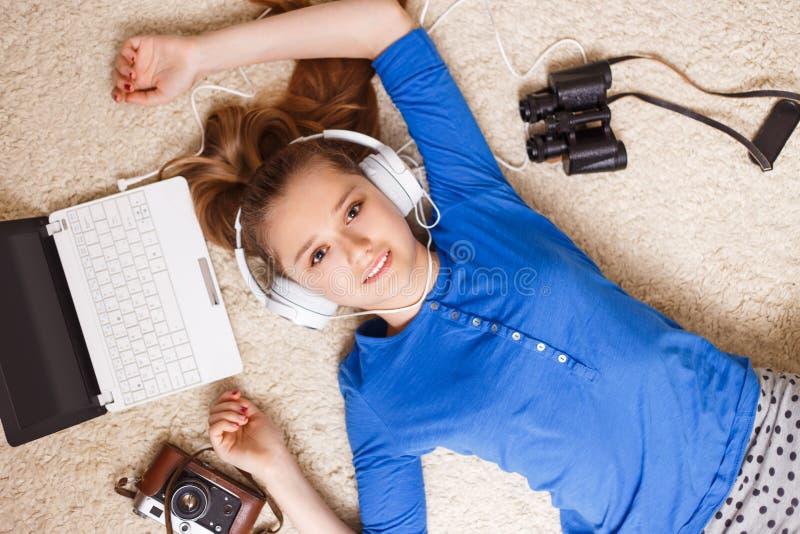 Jonge tiener die op de vloer met laptop liggen royalty-vrije stock foto