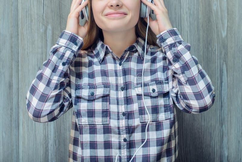 Jonge tiener in geruit overhemd wat betreft hoofdtelefoons en Li stock foto's