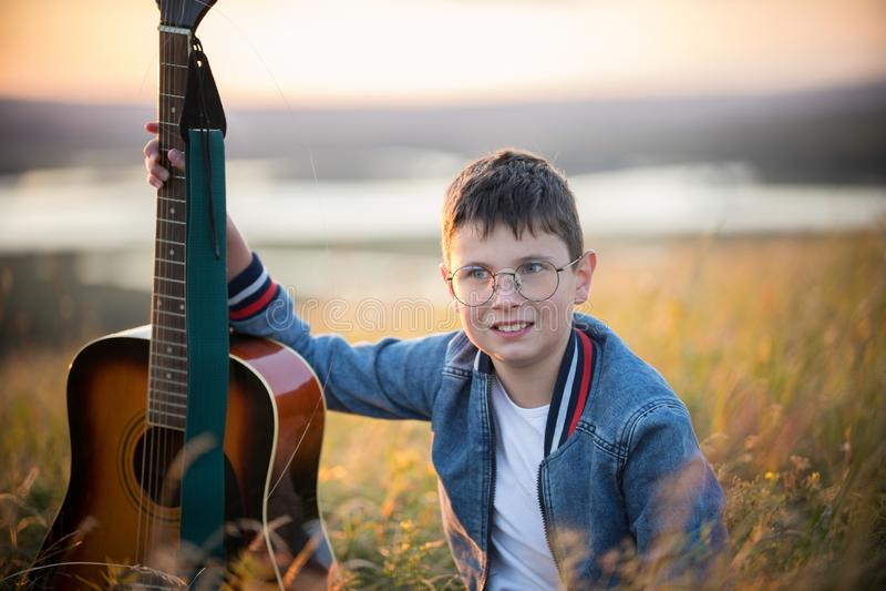 Jonge tienerjongen die akoestische gitaar houden bij de zomergebied bij zonsondergang en het glimlachen stock afbeelding