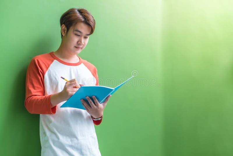 Jonge tienerjongen die op blauw notitieboekje schrijven die bij groene wal leunen stock afbeelding