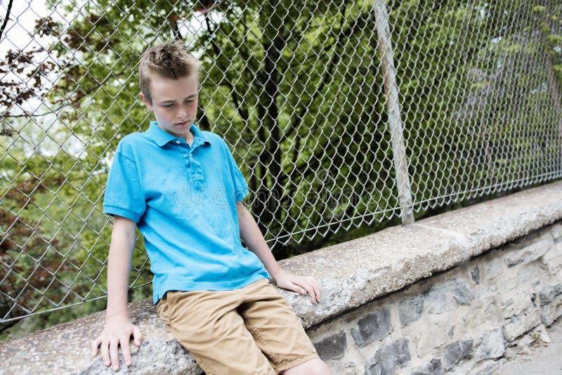 Jonge tienerjongen die uit een omheining kijken royalty-vrije stock afbeelding