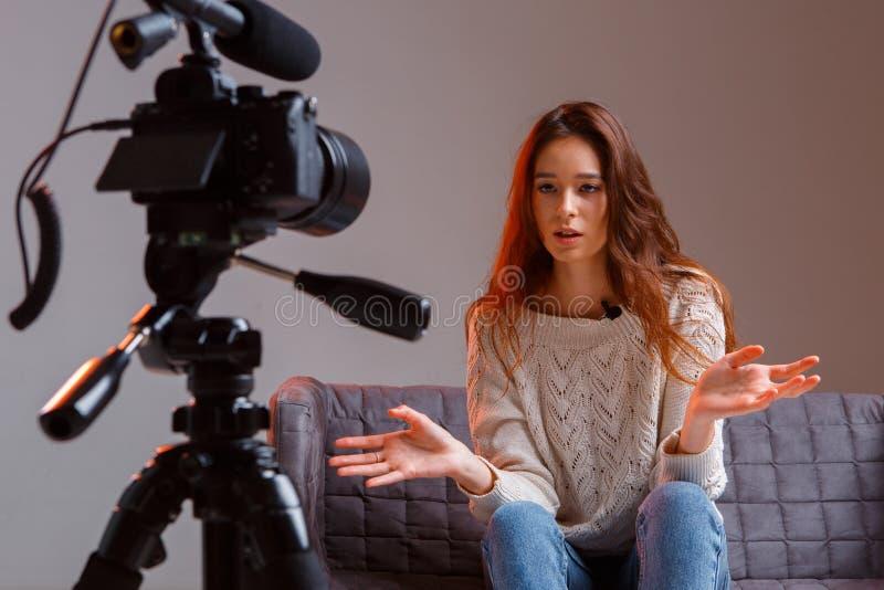 Jonge-tieners-vlogger maakt een video-stream op de bank thuis Een videocamera op een driepoot royalty-vrije stock fotografie