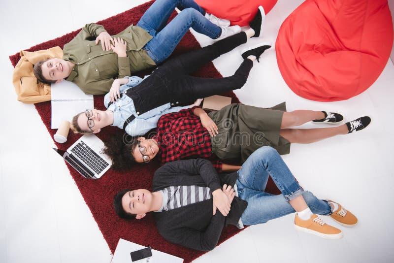 jonge tienerstudenten die op tapijt met notitieboekjes liggen stock afbeelding