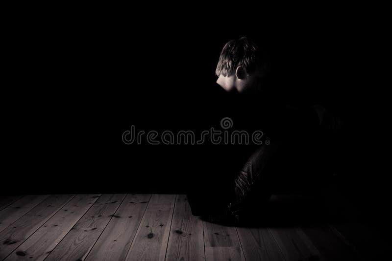 Jonge tienerzitting in duisternis in een zolder royalty-vrije stock afbeeldingen