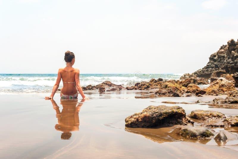 Jonge tienerzitting op het strand van de Atlantische Oceaan stock afbeeldingen