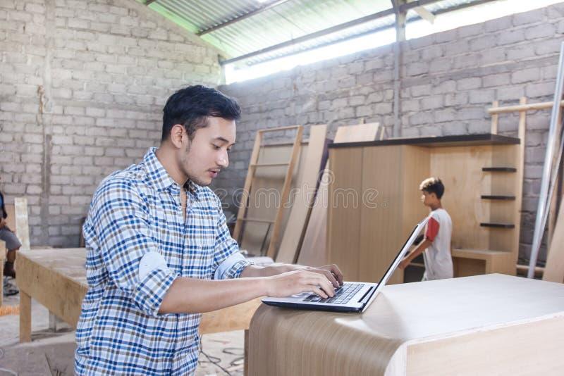 Jonge timmerman die aan zijn laptop werken stock afbeelding