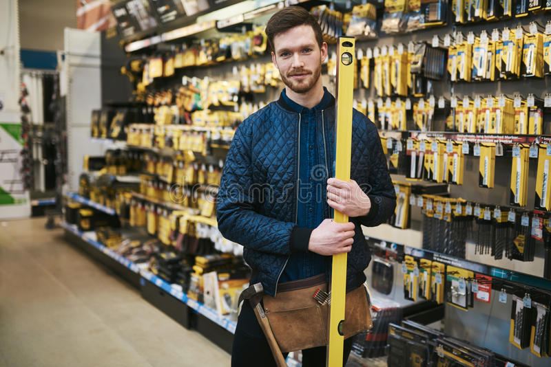 Jonge timmerman die een bouwersniveau houden stock foto