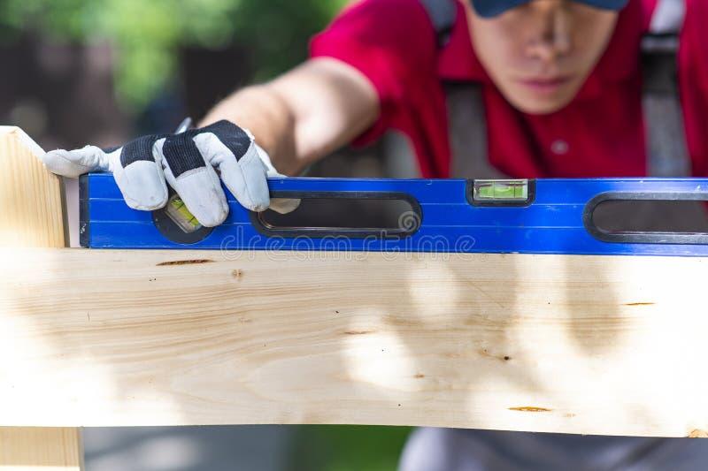 Jonge timmerman die hout meten die waterwaterpas in zijn werk gebruiken stock afbeeldingen