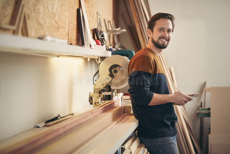 Jonge timmerman die omhoog terwijl het gebruiken van telefoon in zijn workshop kijken stock afbeeldingen