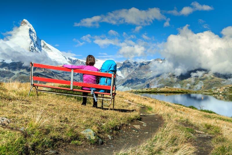 Jonge toeristenvrouw met rugzak het ontspannen op bank royalty-vrije stock foto