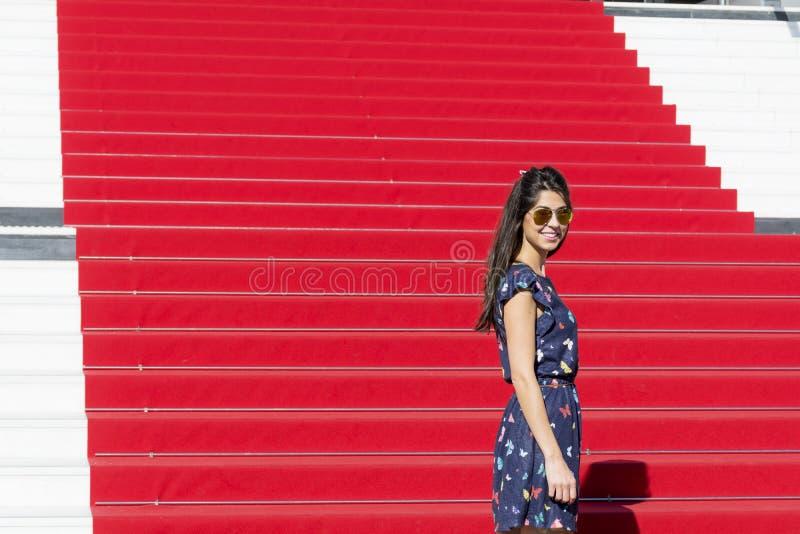 Jonge toeristenvrouw op het Rode tapijt in Cannes, Frankrijk Stairs van bekendheid stock foto
