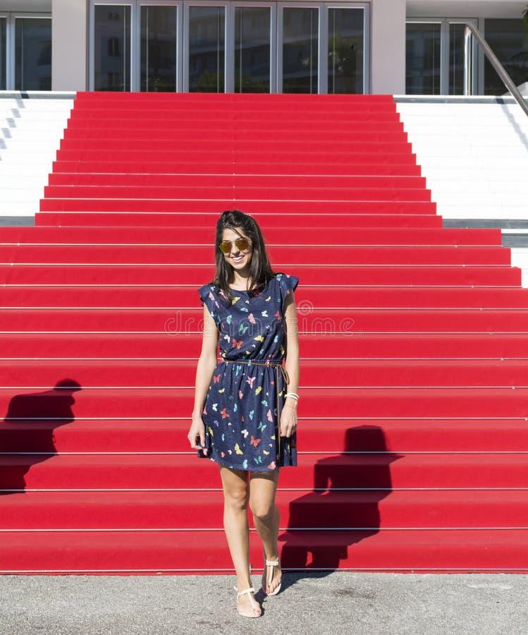Jonge toeristenvrouw op het Rode tapijt in Cannes, Frankrijk Stairs van bekendheid royalty-vrije stock afbeeldingen