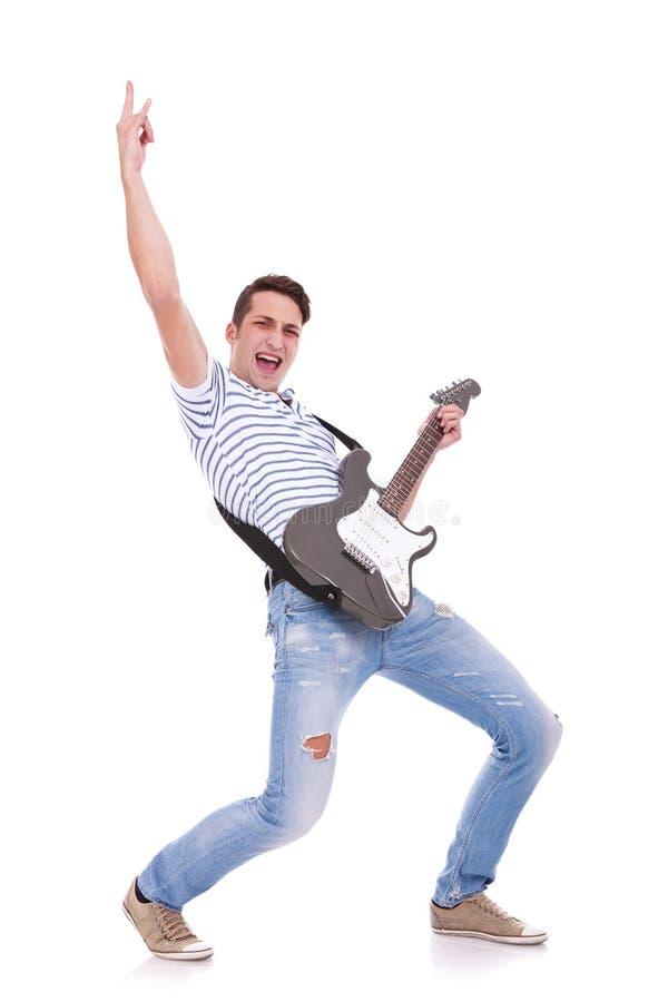 Jonge toevallige mens die een elektrische gitaar speelt stock afbeelding