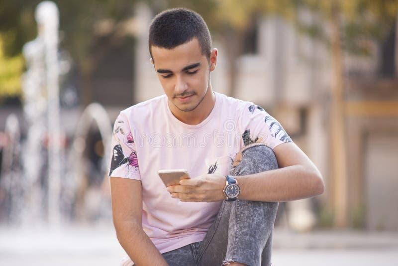 Jonge toevallige mens die en berichten op slimme phon lopen lezen royalty-vrije stock foto