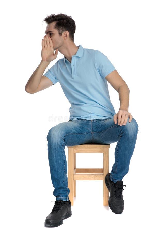 Jonge toevallige mens die en zijn mond fluisteren behandelen stock foto