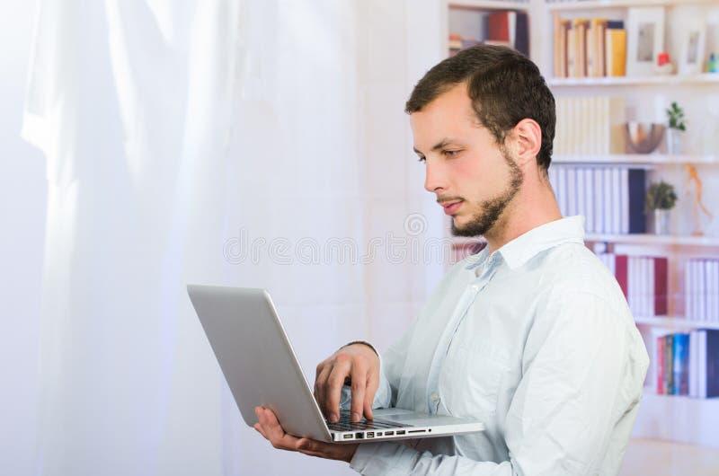 Jonge toevallige mens die laptop met behulp van royalty-vrije stock foto