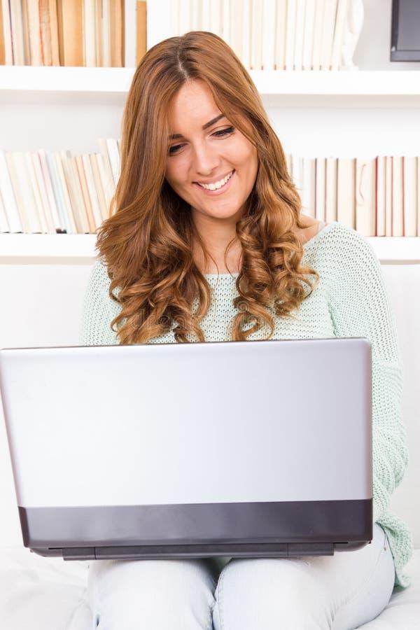 Jonge toevallige mooie vrouw die een laptop computer thuis met behulp van stock foto's