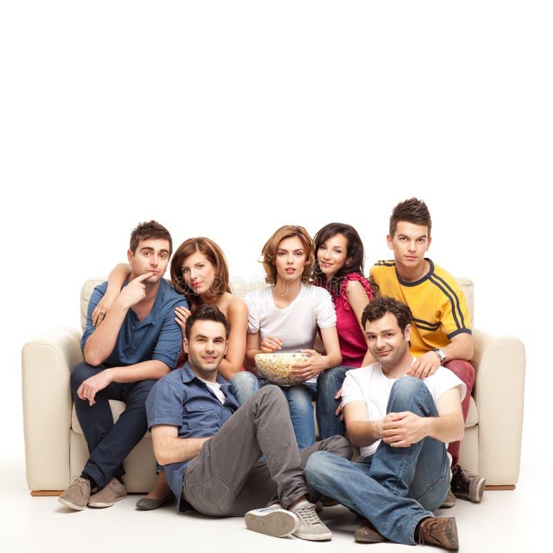 Jonge toevallige vrienden die op televisie letten royalty-vrije stock afbeeldingen